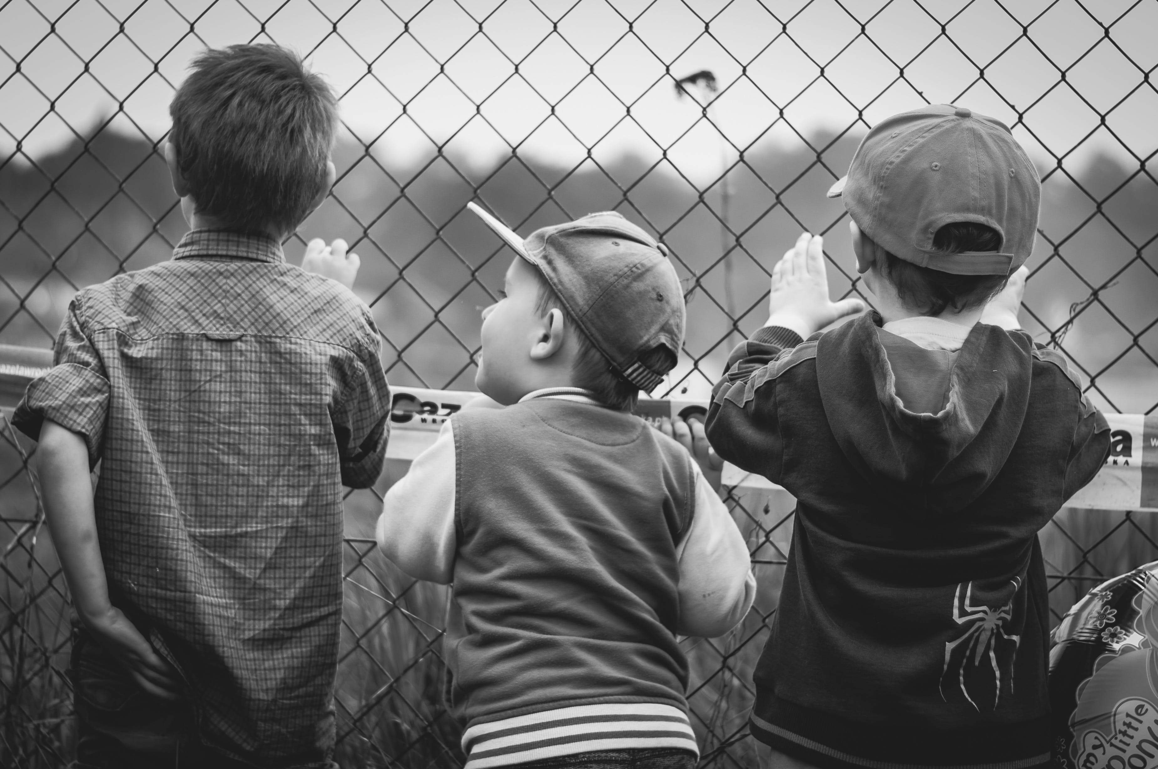 Grayscale Photography of Three Boys Facing Towards Fence