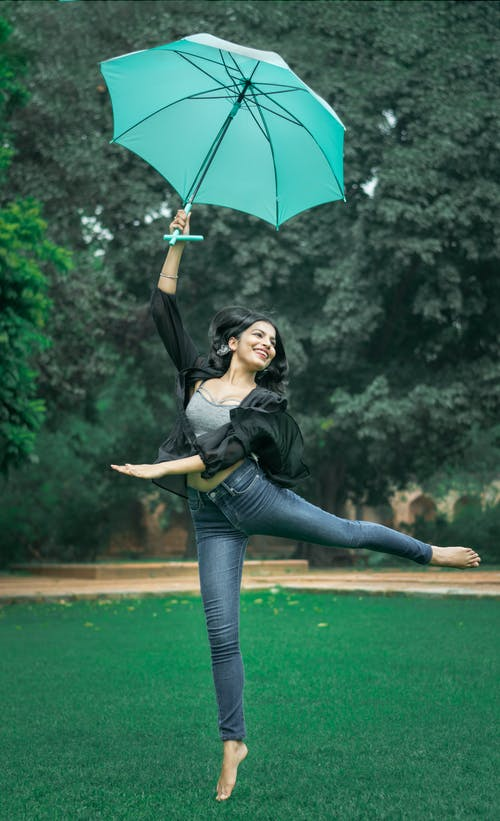 Woman Dancing and Raising Green Umbrella on Grass during Day