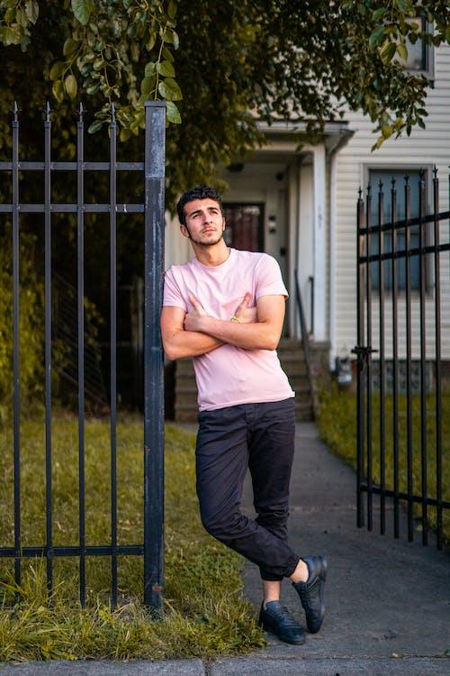Photo of Man Leaning on Black Metal Gate Posing