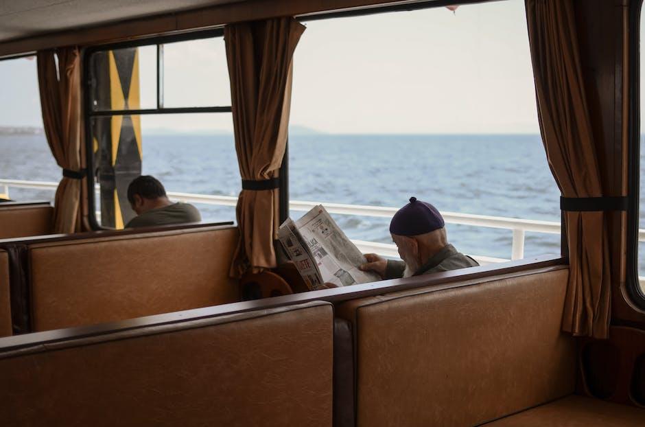 Man sitting on chair reading newspaper