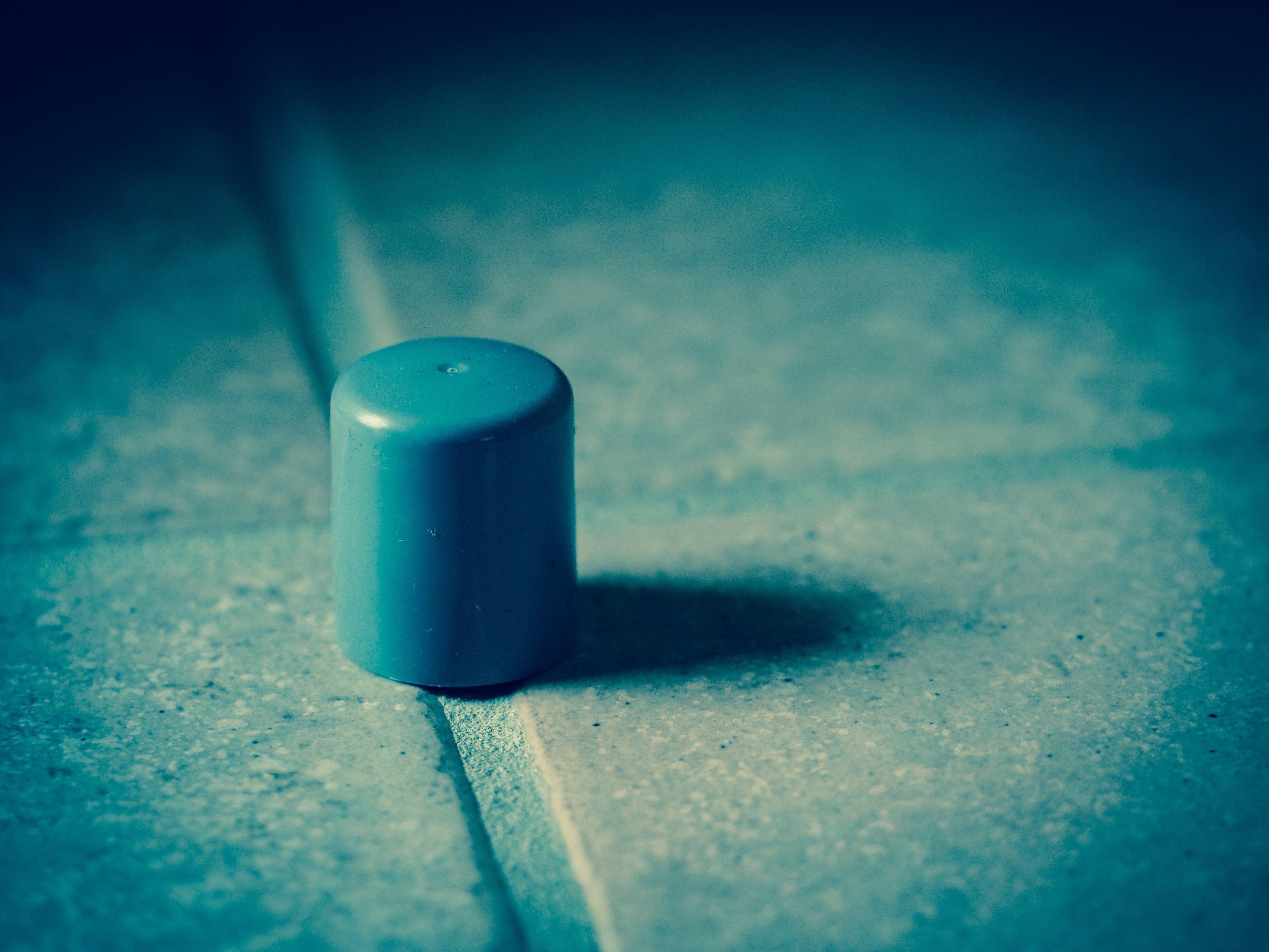 Gray Plastic Cap on Concrete Surface