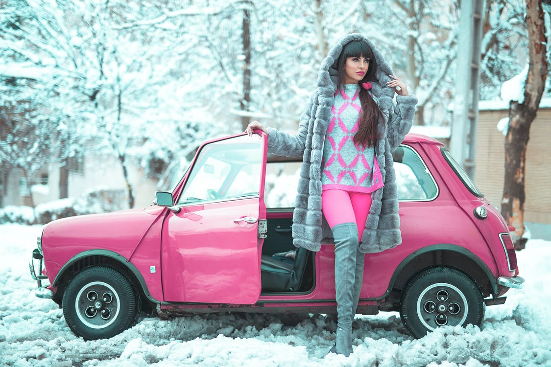 Woman Posing Beside A Pink Car