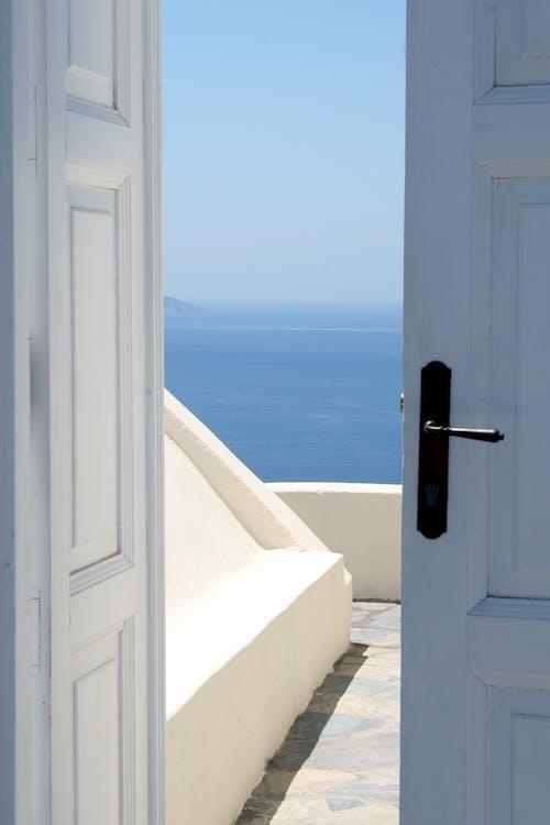 White Wooden Door Near Body of Water