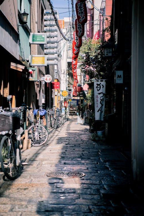 Безкоштовне стокове фото на тему «алея, архітектура, брущатий камінь, велосипеди»