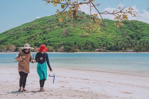 Foto profissional grátis de à beira-mar, andando, ao ar livre, areia