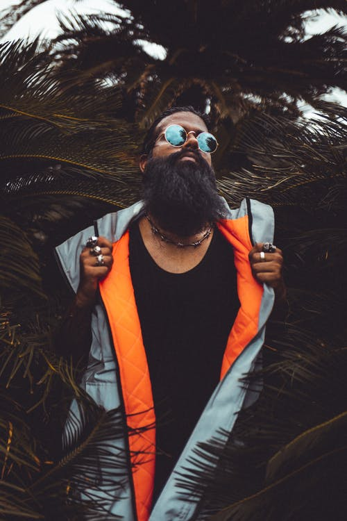 Man Wearing Grey and Orange Zip-up Vest Beside Palm Plant