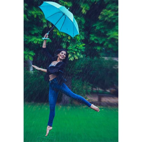 Woman Jumping While Holding Umbrella