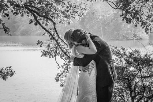 Free stock photo of black and white, couple at lake, couple hugging, happy