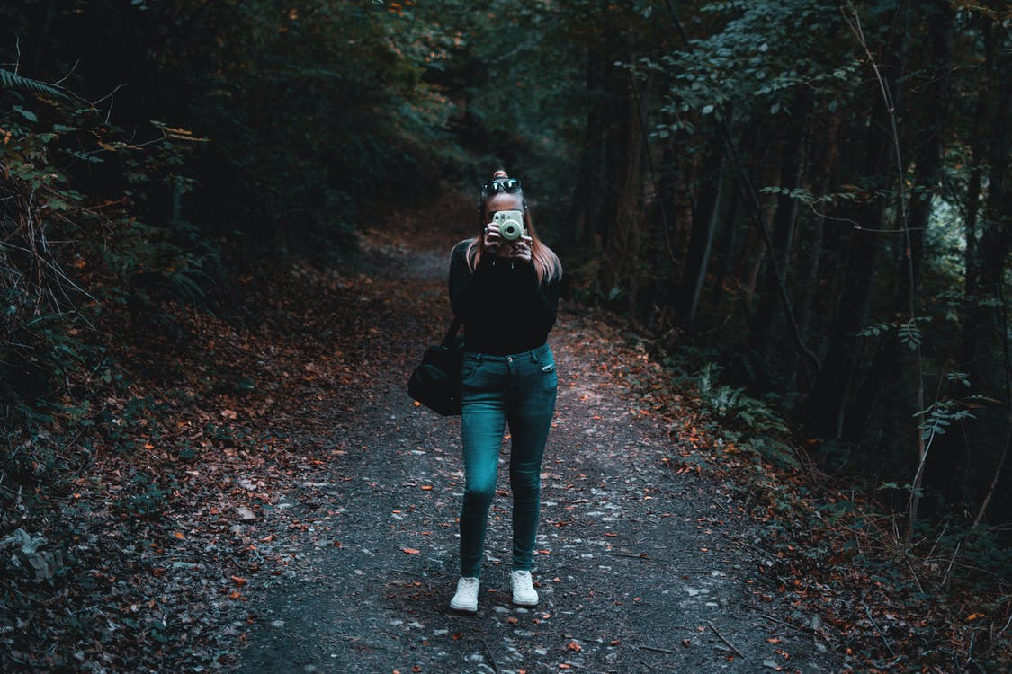 Woman Using Camera While Standing Near Trees