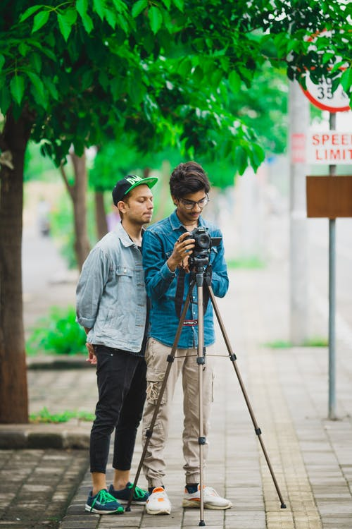 Man Standing Beside Another Man Who Takes Photo