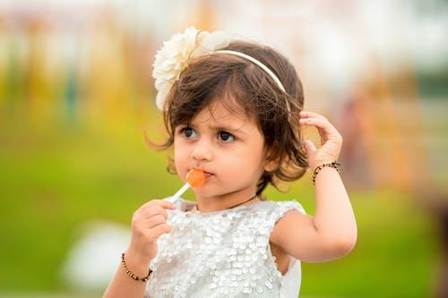 Girl Wearing White Sleeveless Dress Holding a Lollipop
