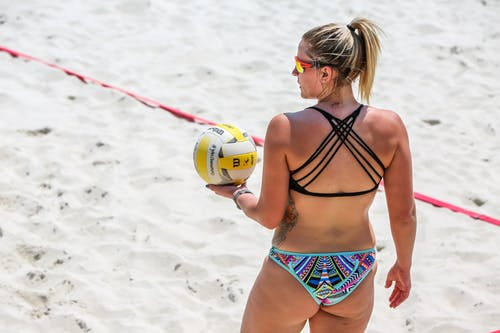 Woman Holding Yellow and White Volleyball