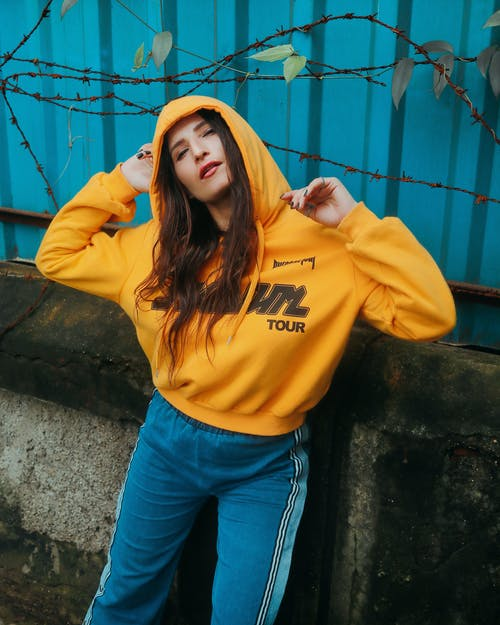 Photo of Woman in Yellow Hoodie and Blue Pants Posing