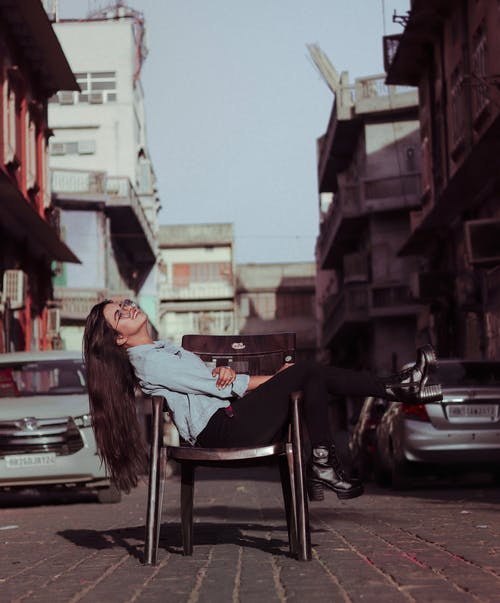 Woman Sitting On A Chair In The Street