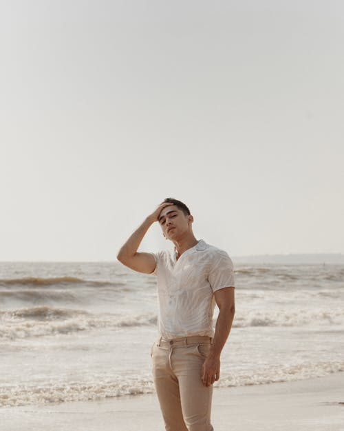 Man Wearing White Shirt and Beige Bottoms Standing Near Seashore