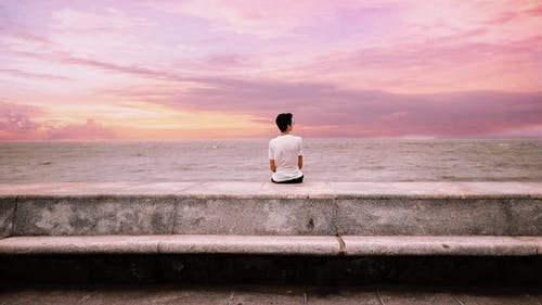 Photo Of Person Sitting On Concrete Platform Near Sea