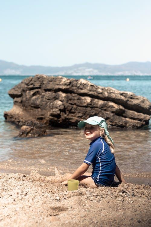 Happy girl sitting on sandy beach