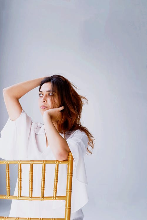 Woman Wearing White Blouse While Leaning on Chair