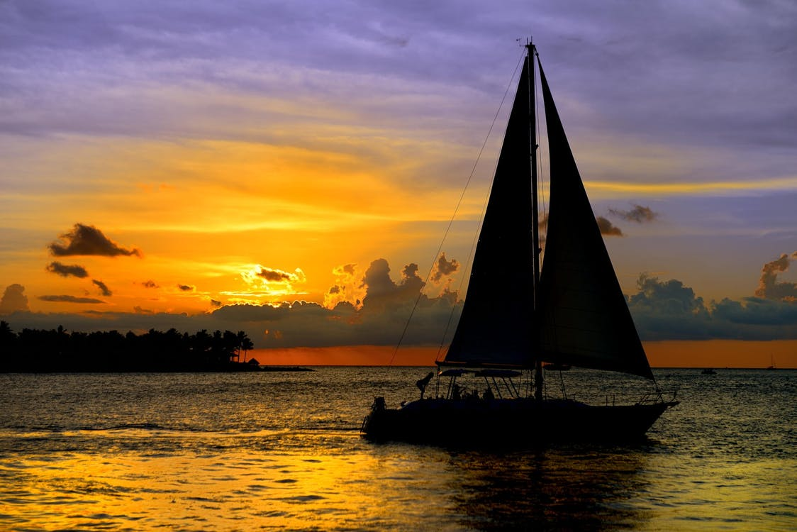 Silhouette Photo of Boat in Golden Hour