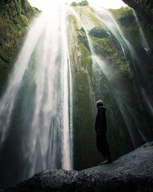 Person Standing Beside Waterfalls
