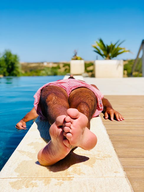 Person lying down beside swimming pool