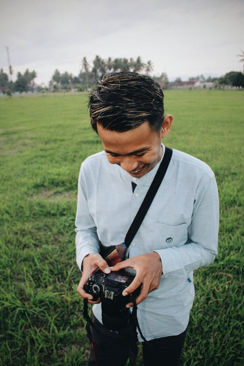 Cheerful guy with photo camera in nature
