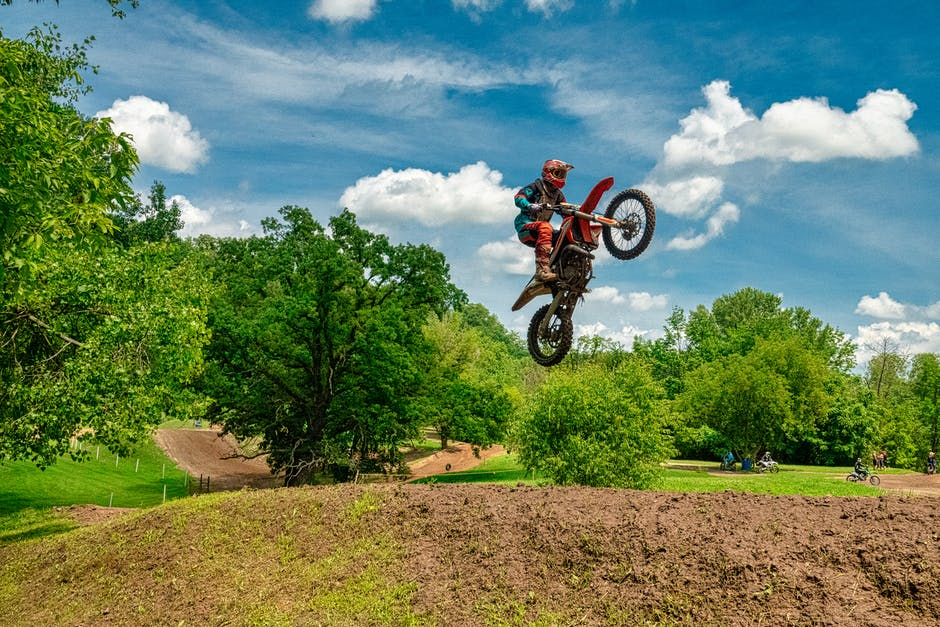 Man riding on black and red motocross dirt bike