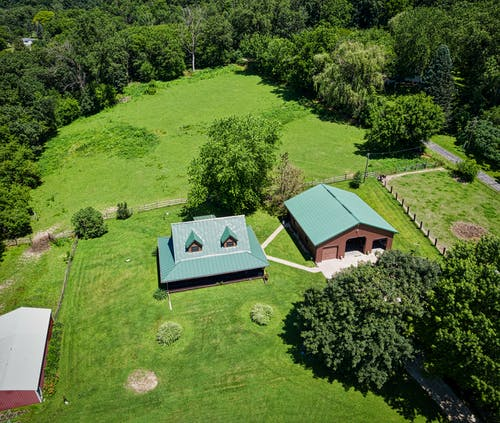Aerial Photo of House Surrounded by Luscious Land