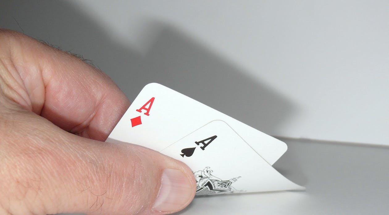 Person Touching Ace of Spades and Ace of Diamonds Playing Cards