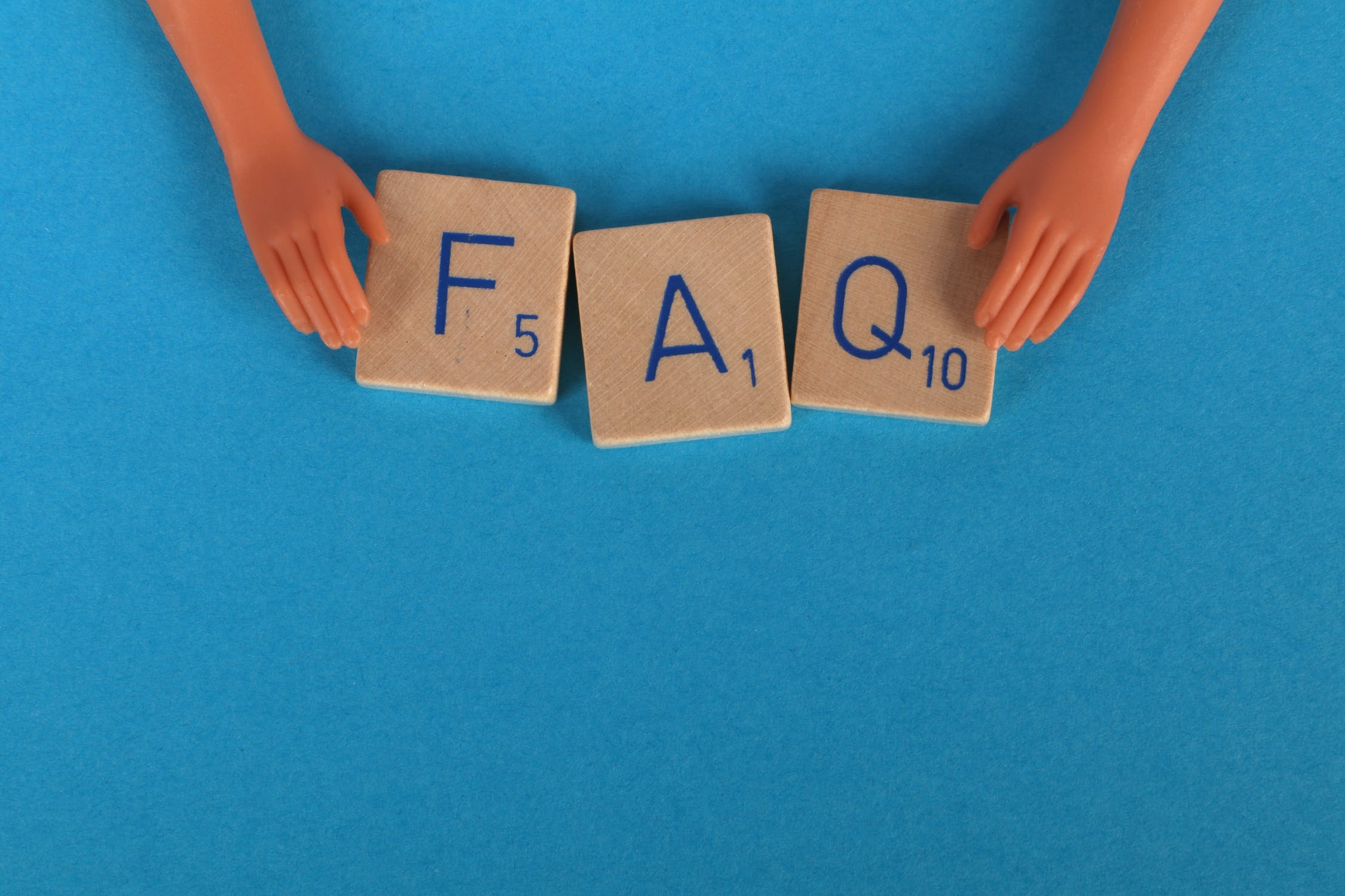 "Doll hands arrange scrabble letters into order reading ""FAQ"" on a light blue background. Photo used courtesy of Pexels.com."