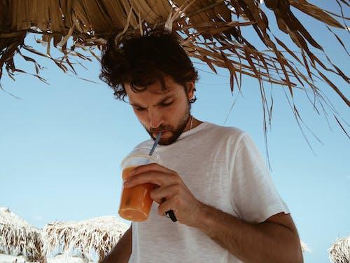 Man Sipping Orange Drink