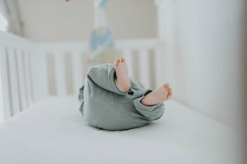 Close-up Photo of Baby Wearing Gray Pants