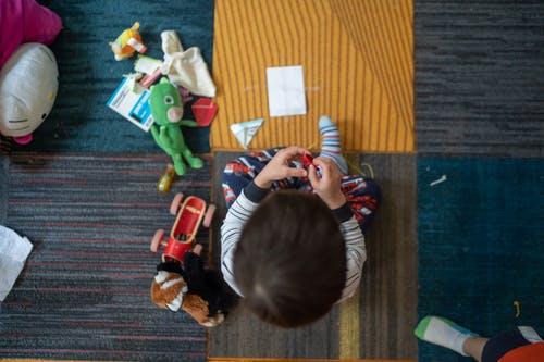Top-view Photography of Toddler Playing With Toy
