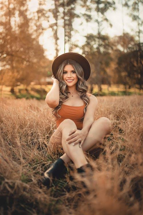 Woman In Orange Top Sitting In A Grass Field