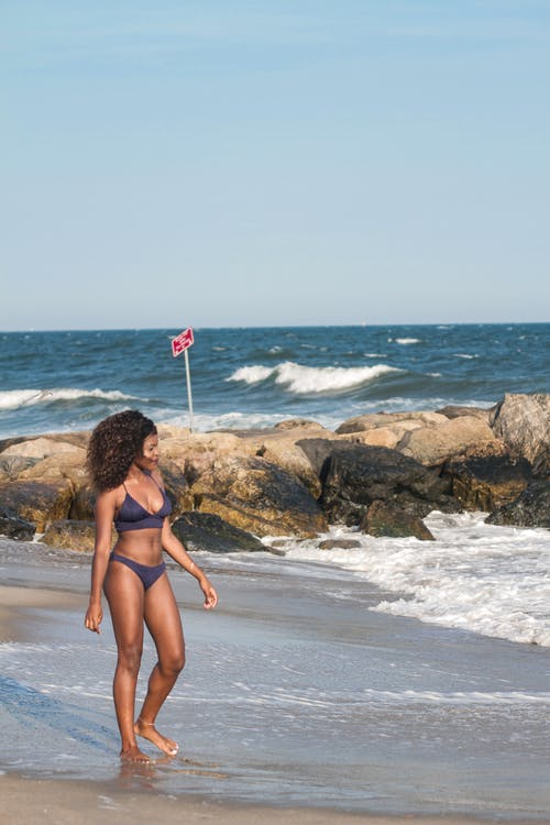 Photo of Woman in Purple Bikini Walking on Seashore