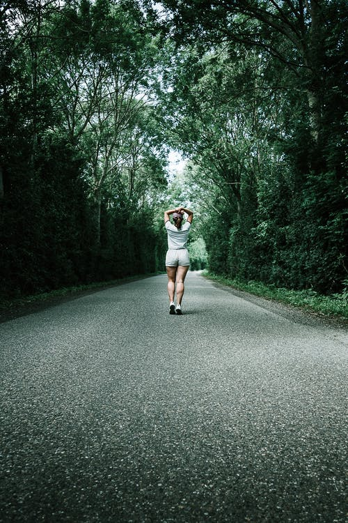 Woman in White T-shirt Walking on Concrete Road