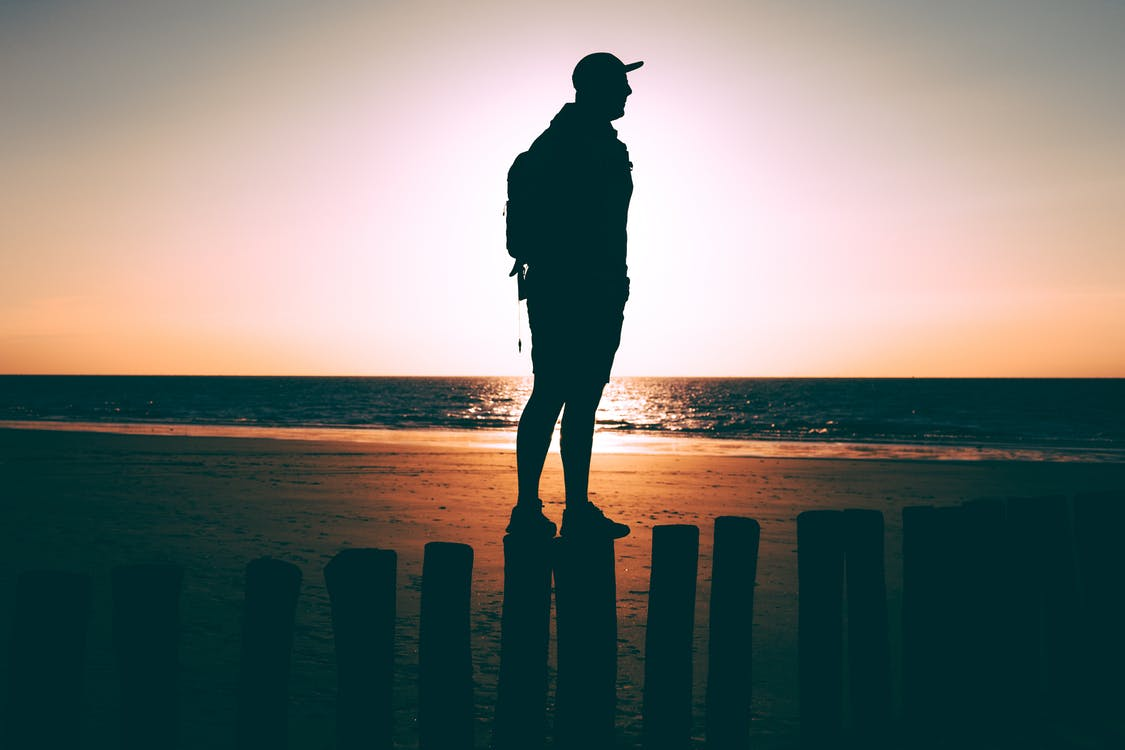 Man Standing On Posts On Seashore During Golden Hour