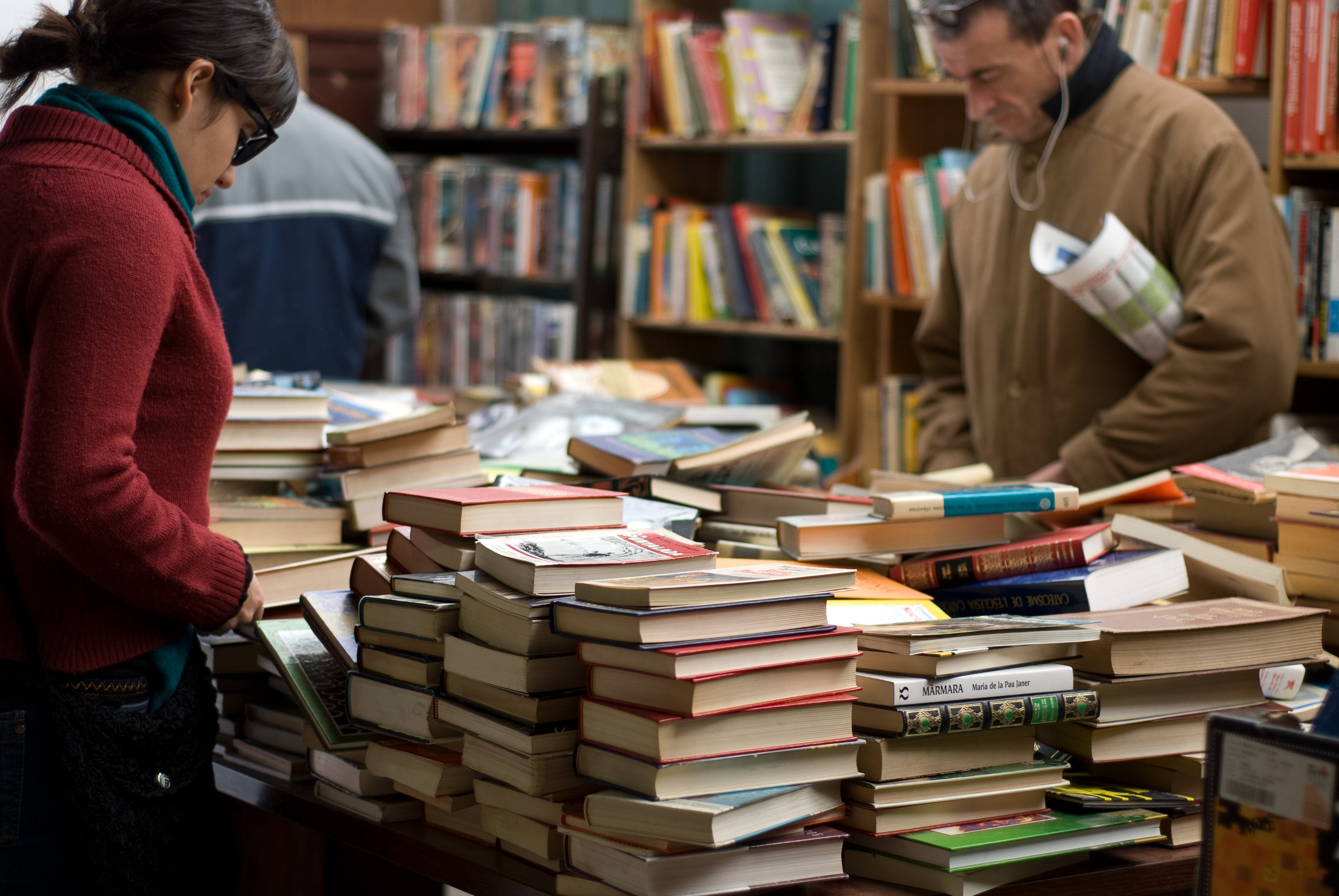 Woman and Man Standing Beside Piles of Books