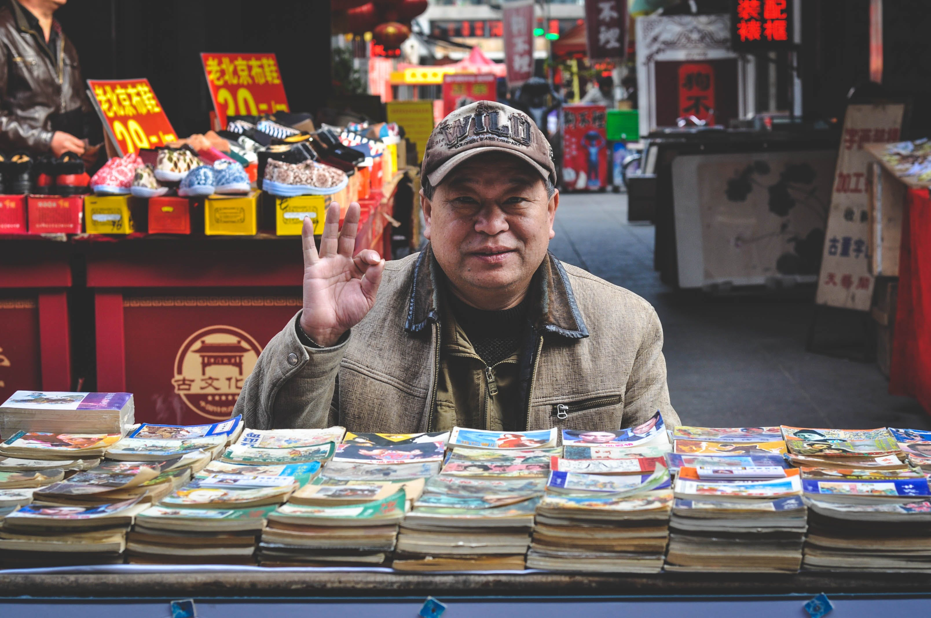 Man in Brown Coat in Front of Books