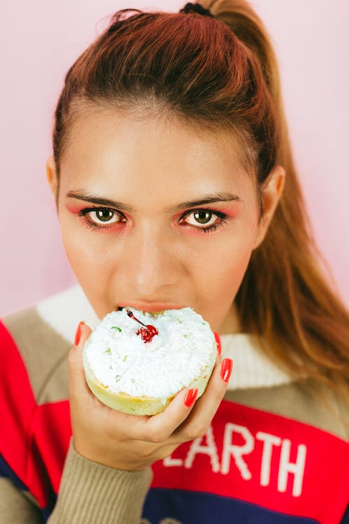 Close-up Photo of Woman Eating Pastry
