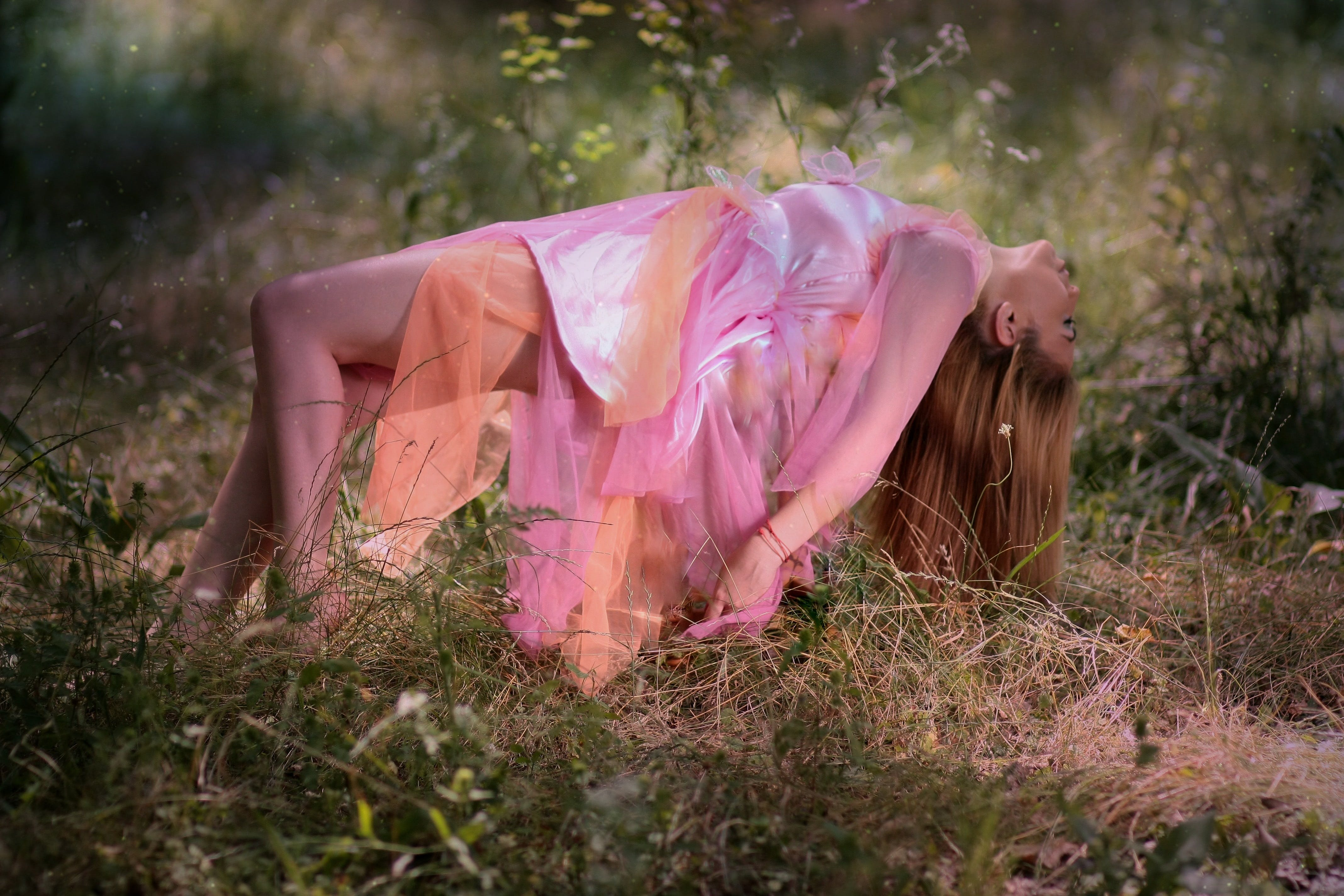 Woman Wearing Pink and Orange Dress While Lying on Grass Field