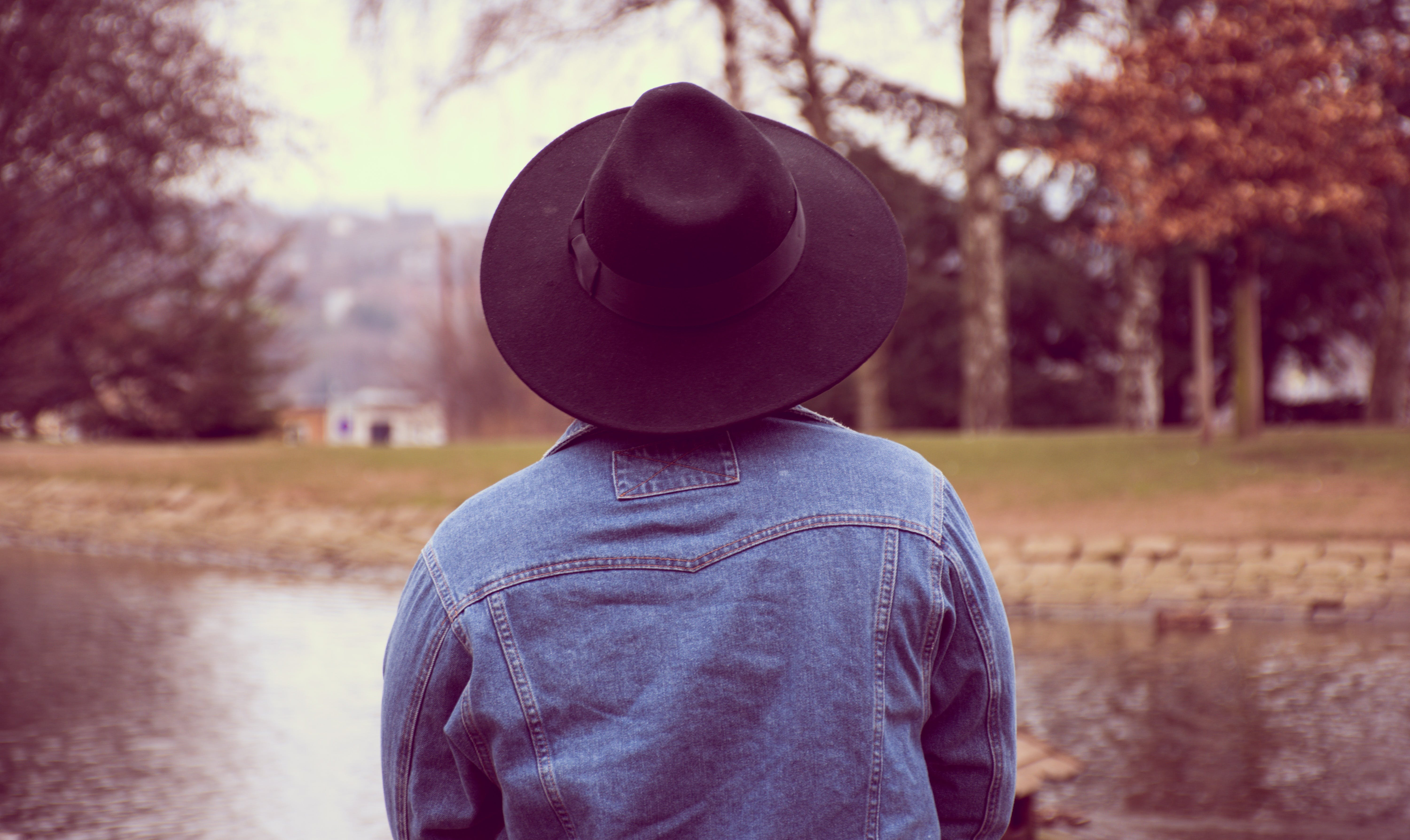 Person Wearing Blue Denim Jacket and Hat Watching the Body of Water