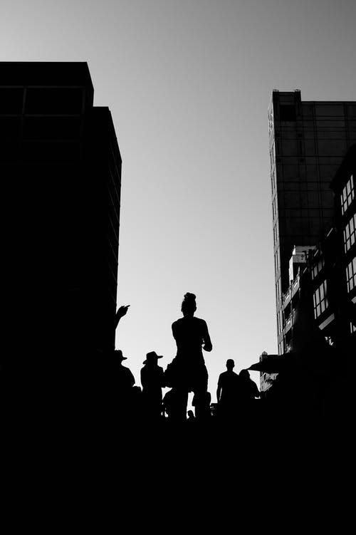 Silhouette of People Standing  Near Buildings