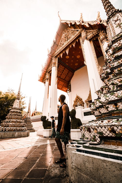 Photo of a Man Standing Near Temple
