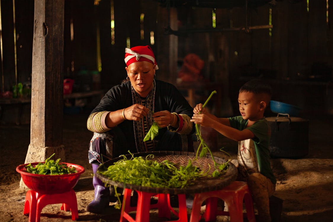 Photo of Woman and Boy Sitting and Cleaning Vegetables