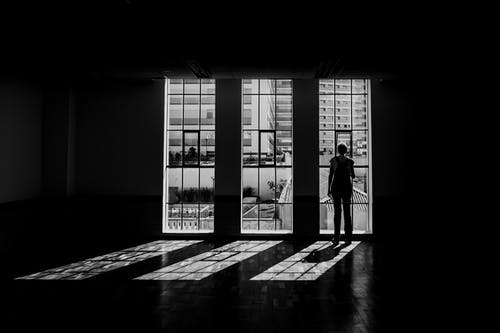 Silhouette Of Person Standing Facing Window