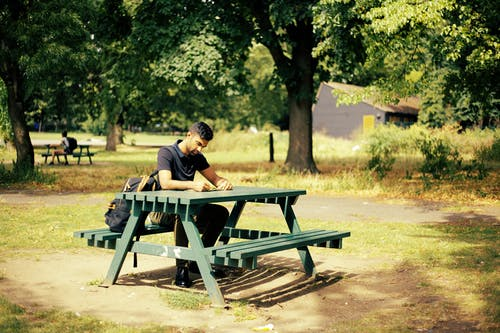 Man Sitting  on a Green Picnic Table Reading a Book