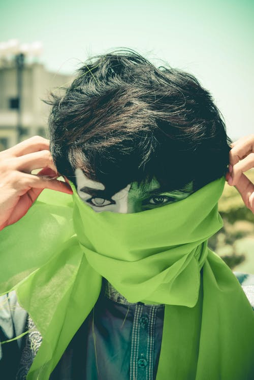 Person Covering Face With Green Cloth