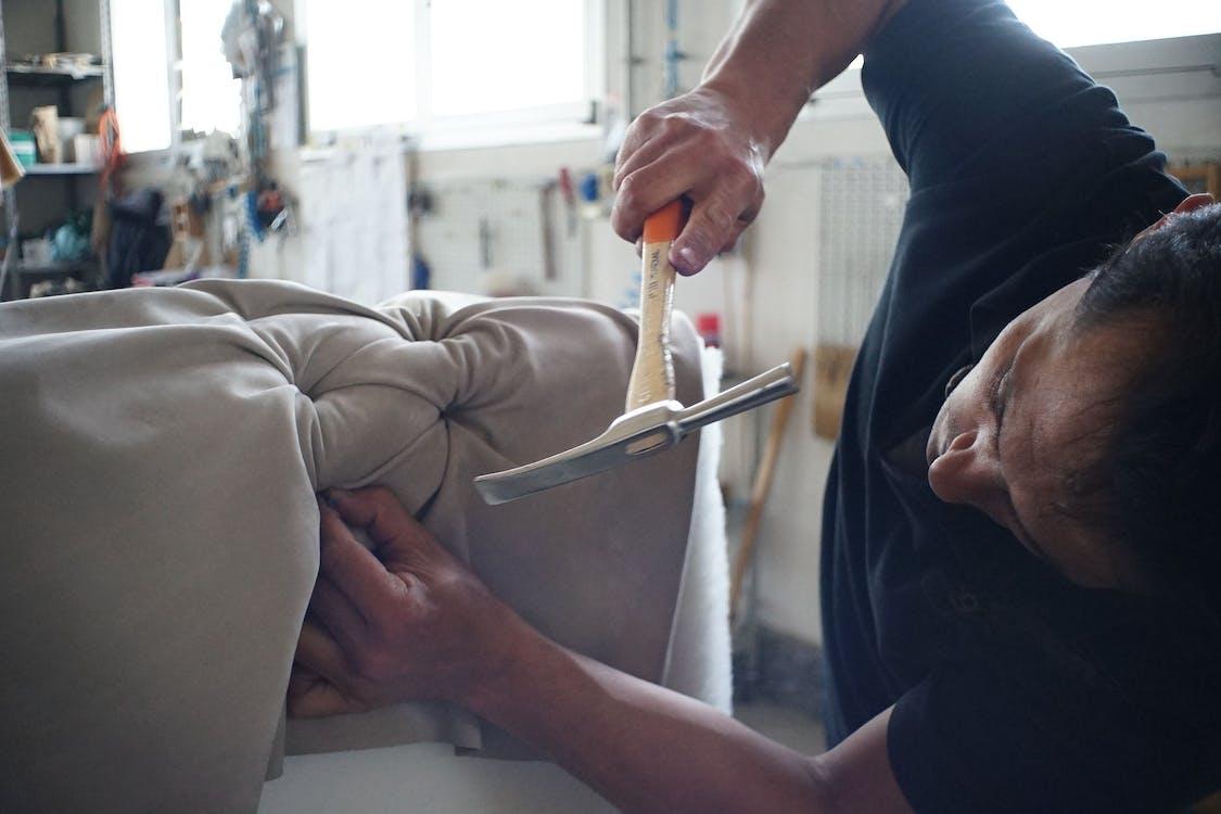 Man Holding Hammer and Nail Repairing Sofa