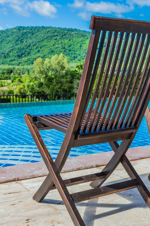 Brown Wooden Deck Chair in Front of Pool